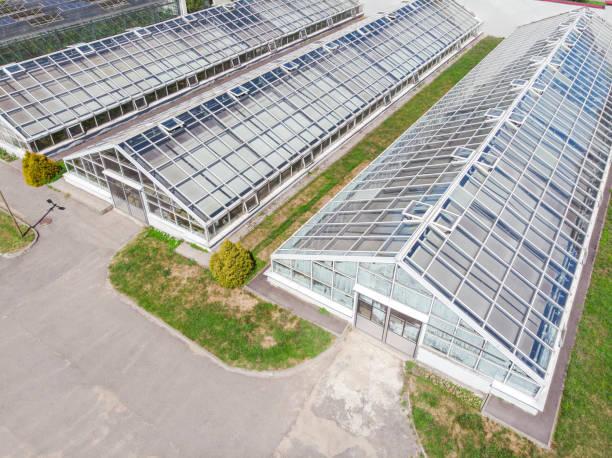 rij van glazen kassen voor plantaardige productie - kas bouwwerk stockfoto's en -beelden