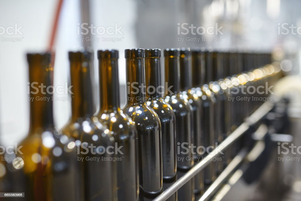 Row of glass wine bottles moving by conveyor stock photo