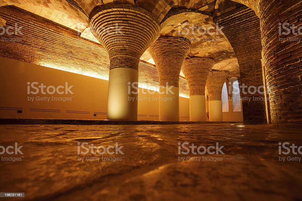 Row of golden illuminated ancient round brick columns and arches royalty-free stock photo