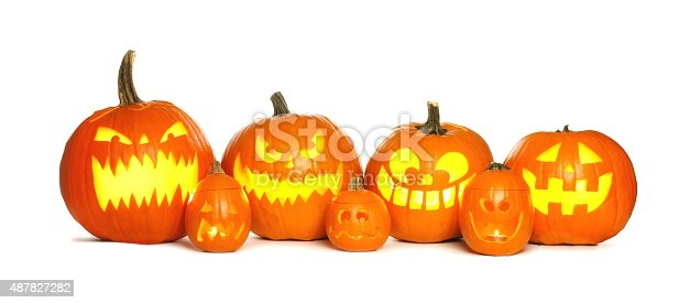 Row of fun lit Halloween Jack o Lanterns isolated on a white background