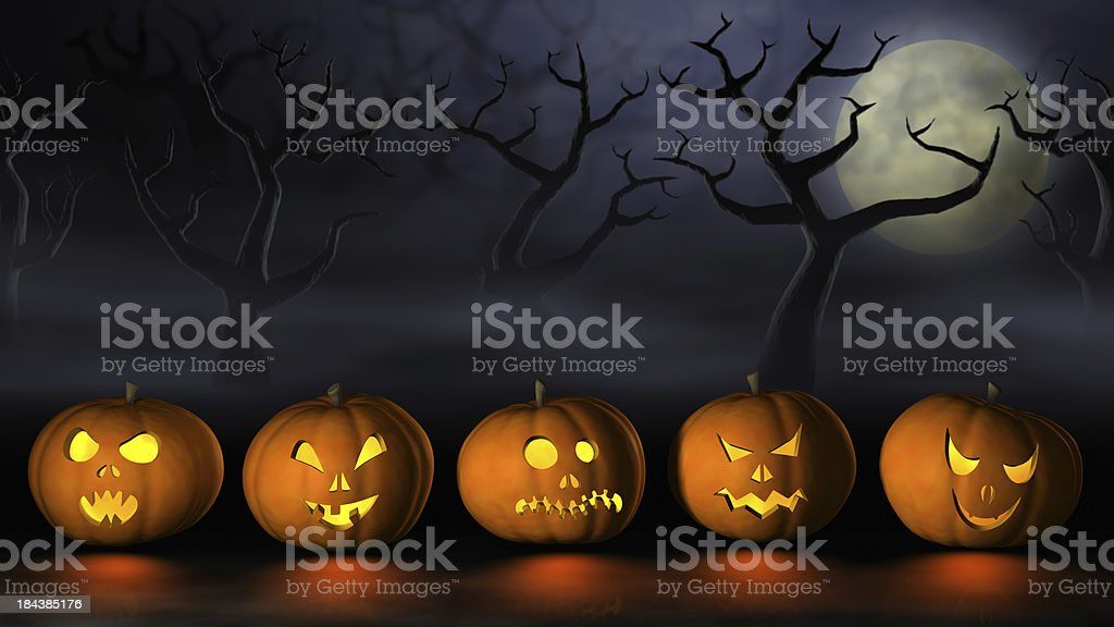 Row of Halloween pumpkins in a spooky forest at night royalty-free stock photo