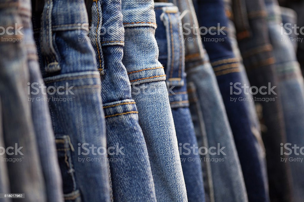 Row of hanged blue jeans in a shop stock photo
