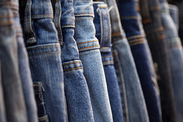 row of hanged blue jeans in a shop - jeans stock photos and pictures