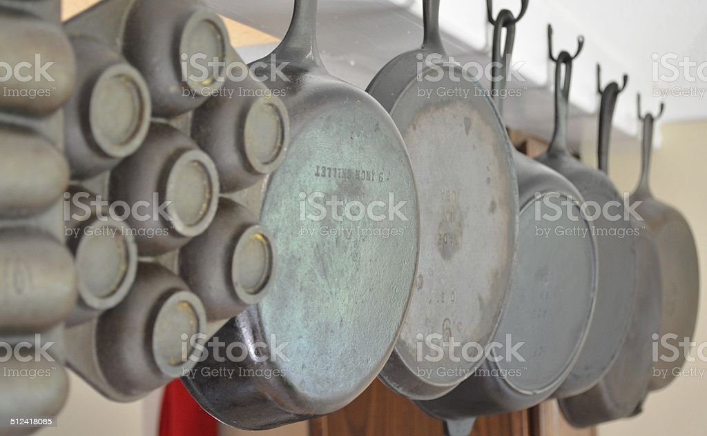 Row of hanging cast iron skillets stock photo