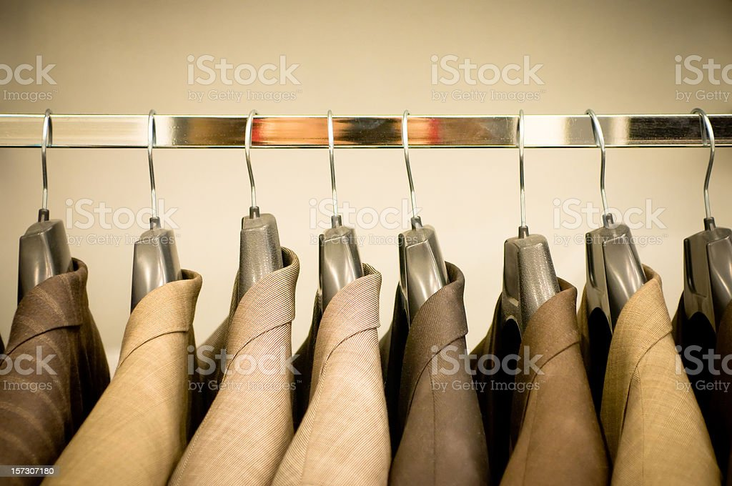 Row of hanging suits in wardrobe stock photo