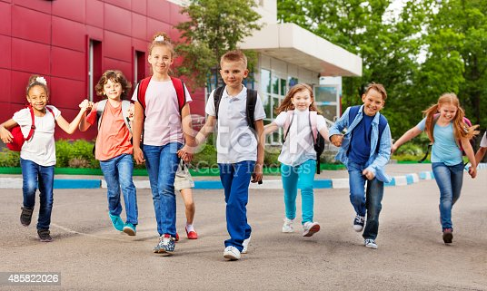istock Row of happy kids with bags near school building 485822026