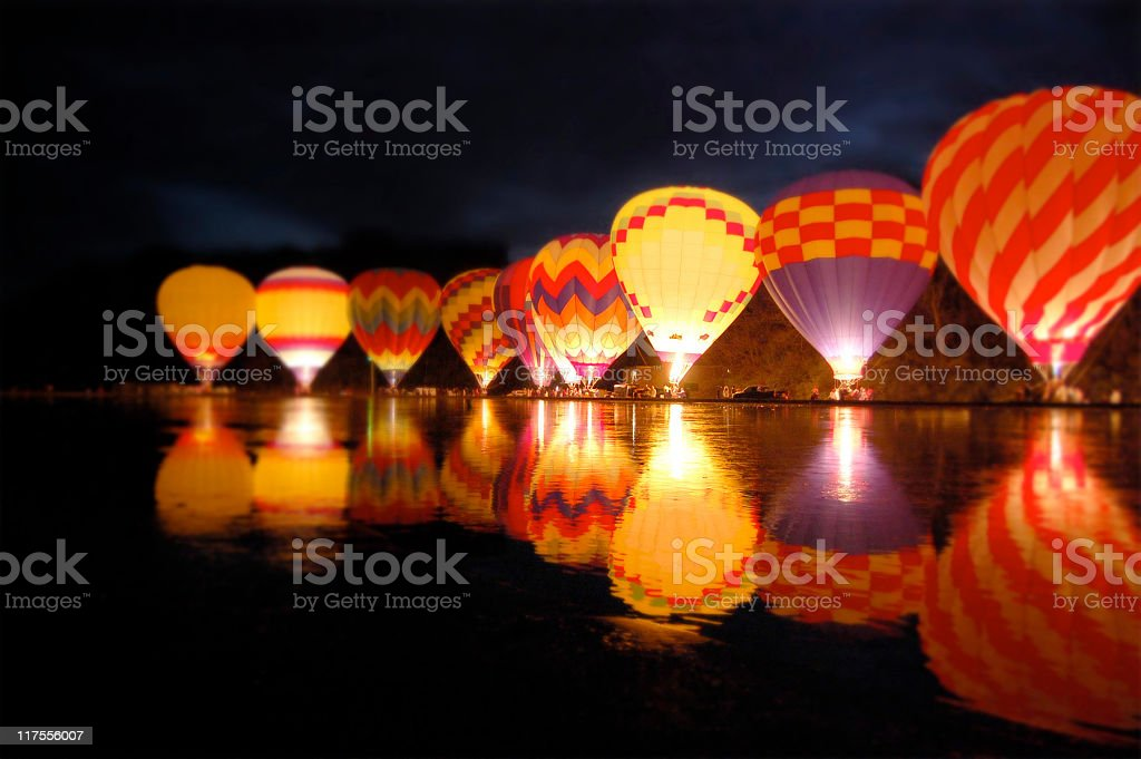 Row of hot air balloons lit up at night beside a lake stock photo