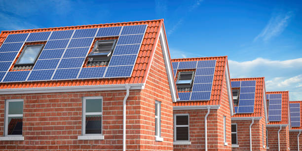 Row of house with solar panels on roof  on blue sky background. stock photo