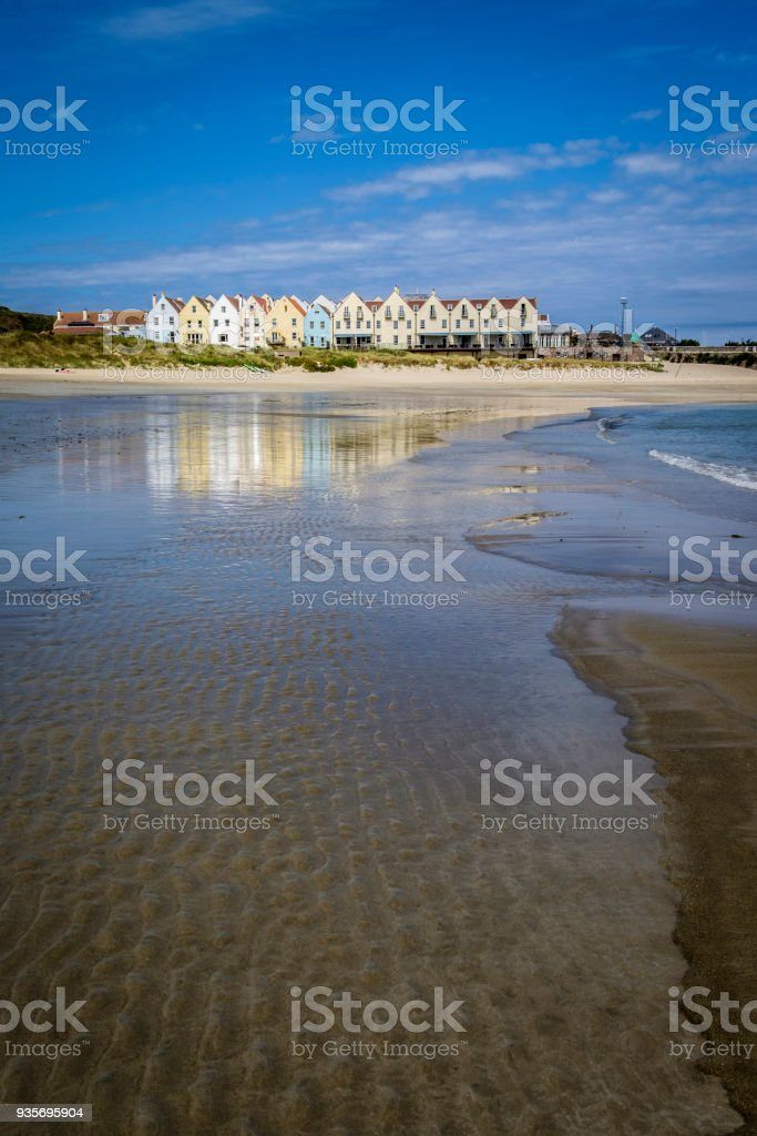 Row of houses and a hotel, reflected in the water at Braye Beach, Alderney, Guernsey, Channel Islands stock photo