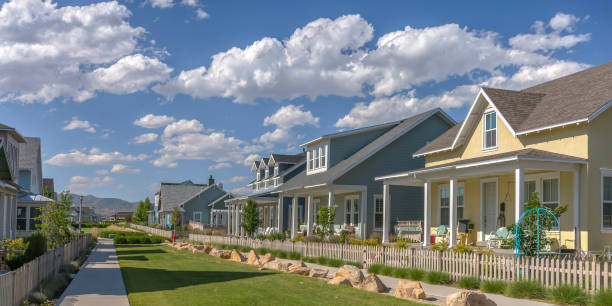 row of houses under blue sky and puffy clouds - residential district stock pictures, royalty-free photos & images