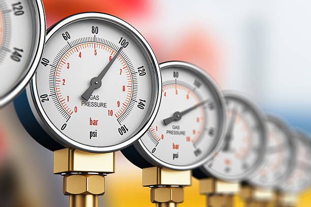 Row of industrial high pressure gas gauge meters See also: meter instrument of measurement stock pictures, royalty-free photos & images