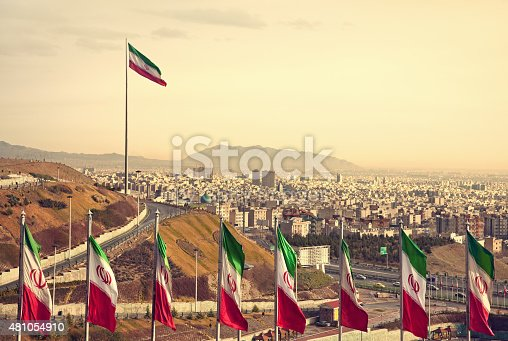 Set of Iran flags in Front of Tehran Skyline and one large flag in the background at sunset with orange warm tone.