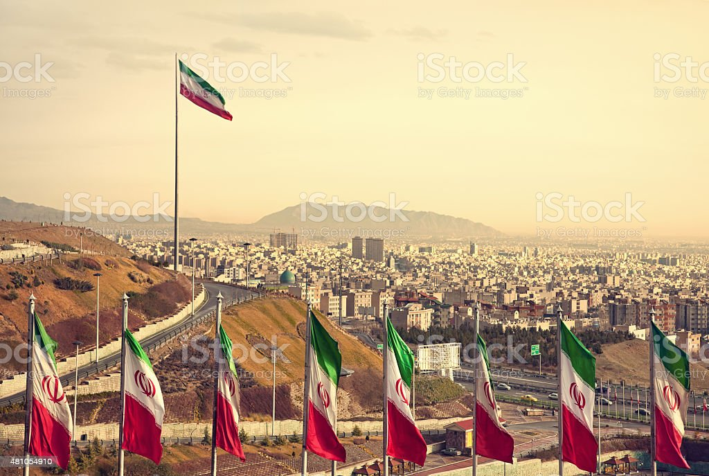 Row of Iran Flags in Front of Tehran Skyline stock photo