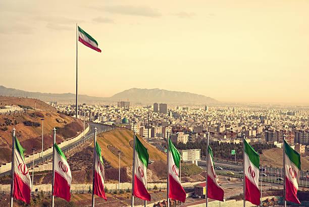 row of iran flags vor teheran auf die skyline - iranische stock-fotos und bilder