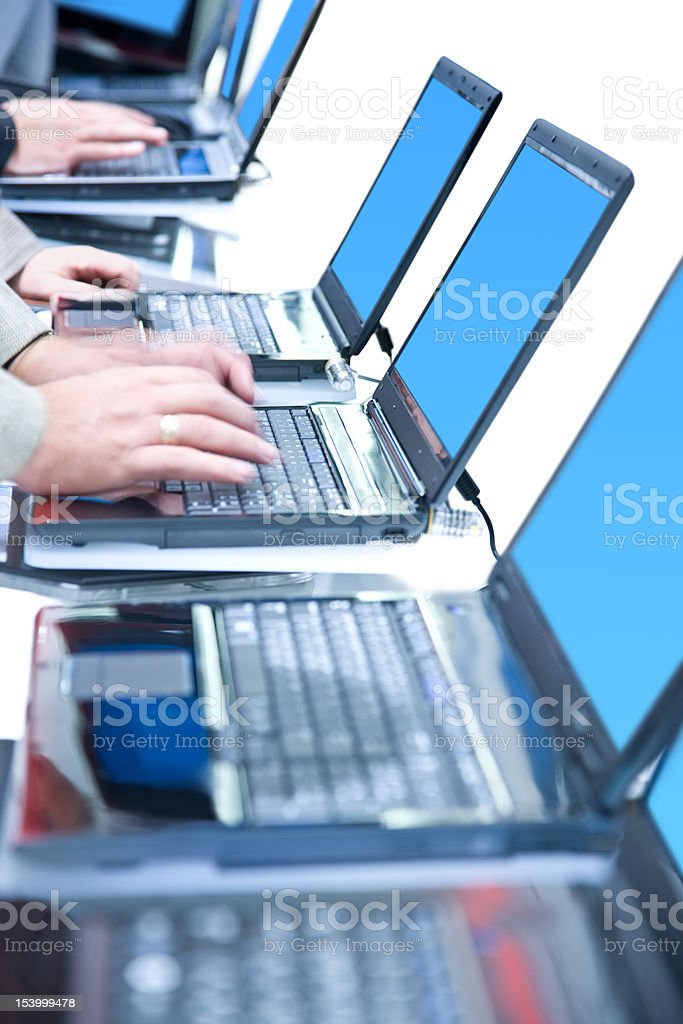 Row of laptops with hands on them, isolated royalty-free stock photo