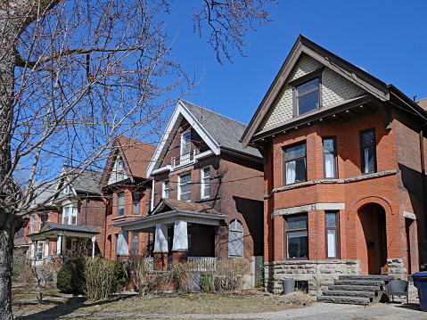 Row of large old Victorian style detached brick houses with gables