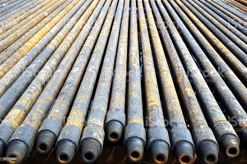 A row of long dirty steel drill pipes stock photo