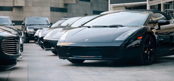 Row of luxury sports coupe cars for sale on display outside of a car dealership store in Besiktas, Istanbul, Turkey. Maseratti, Ferrari, Range Rover, BMW, Audi, Lamborghini, Mercedes
