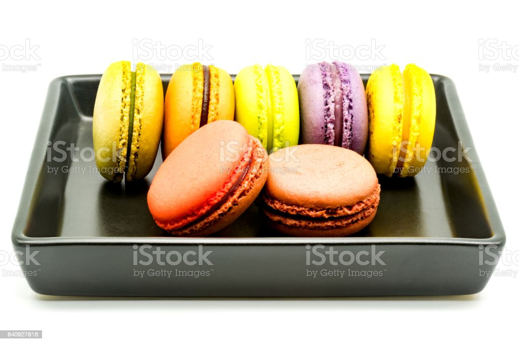 Row of macarons in a black plate stock photo