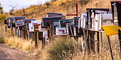 Row of mailboxes on a grassy roadside. Metal mailboxes placed in a row on a grassy ground beside a road. The grassy terrain continues into a slope behind the sunlit mailboxes.