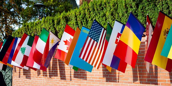 Row of many different flags hanging from a brick wall during the day. Representing of countries Multi cultural event, mix of culture patriotic symbols, many nationalities, nations abstract concept.