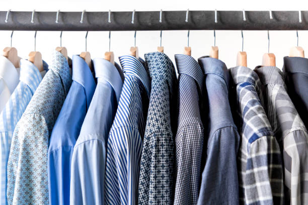 Row of men's shirts in blue colors on hanger Row of men's shirts in blue colors on hanger on white background coathanger stock pictures, royalty-free photos & images