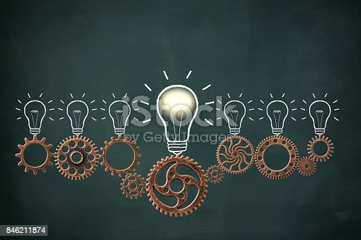 istock Row of metal gears and illuminated light bulb drawn on blackboard 846211874