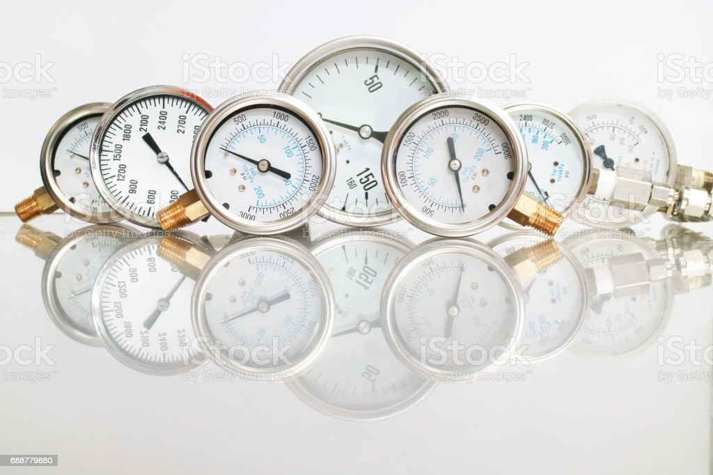 Row of metal steel high pressure gauge meters or manometers with brass fittings on tubing pipeline at LNG or LPG natural gas distribution station plant or factory facility isolated on white background.Pressure gauge in oil and gas production process. stock photo