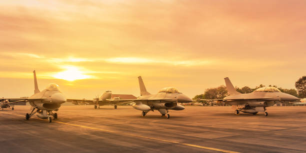 Row of military fighter jet aircraft parked on runway on sunset Row of military fighter jet aircraft parked on runway in the base airforce standby ready to take off for military mission on sunset military base stock pictures, royalty-free photos & images
