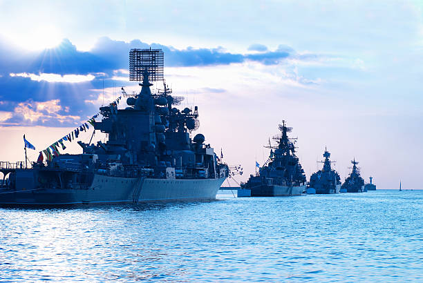 row of military ships at the sea during sunset - marines stock photos and pictures