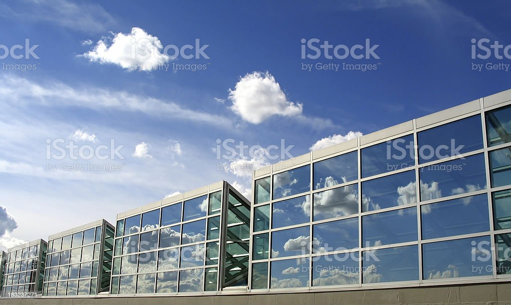 Row of modern glass buildings with a slightly cloudy sky royalty-free stock photo