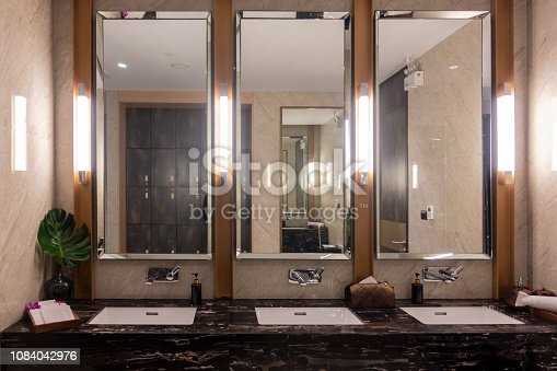 istock Row of modern marble ceramic wash basin in public toilet, restroom in restaurant or hotel or shopping mall, interior decoration design 1084042976