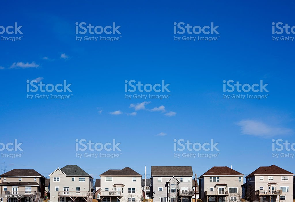 Row of modern townhouses against bright blue sky stock photo
