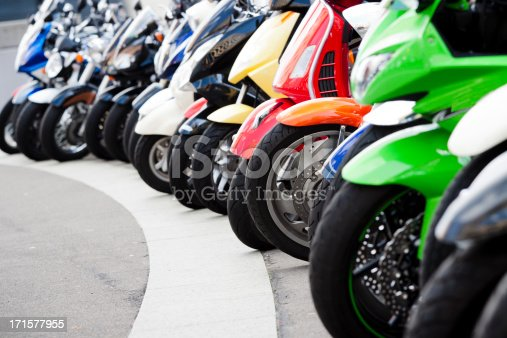 Closeup row of colourful motor scooters standing on the street, full frame horizontal composition with copy space