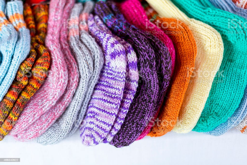 row of multicolored hand-knitted baby socks stock photo