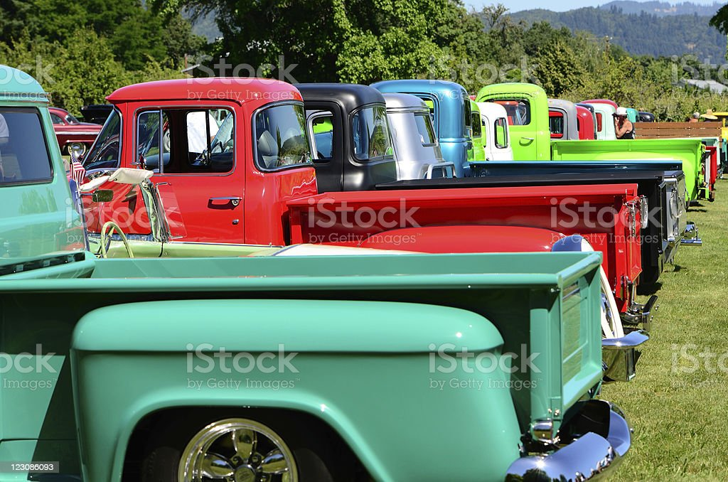 Row of multicolored vintage trucks on a sunny day stock photo