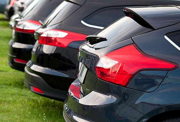row of new ford focus vehicles at dealership - ford focus stock photos and pictures