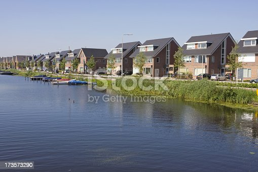 istock A row of new houses lining a body of water with boats in it 173573290