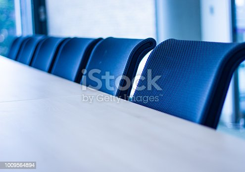 Row of office chairs in a meeting room shot from an angle