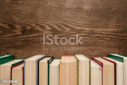 istock Row of old books with colorful covers on brown wooden background. Education concept. Mock up for different ideas. Empty place for text, quote or sayings. Front view. 1074228168