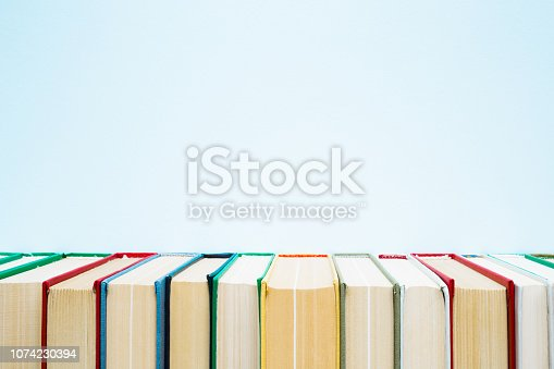istock Row of old books with colorful covers on pastel blue background. Education concept. Mock up for different ideas. Empty place for text, quote or sayings. Front view. 1074230394