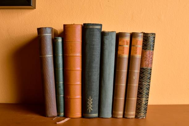 Row of old  bound books. Antique books on yellow and claret background stock photo