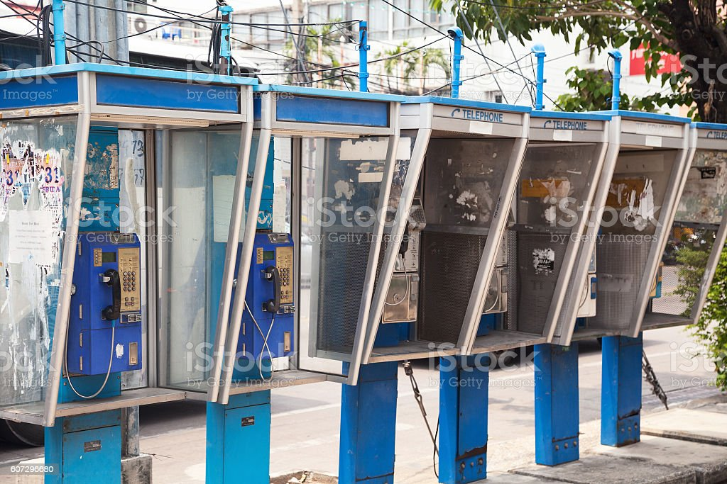 Row of old dirty payphones. Group of messy telephone booths stock photo