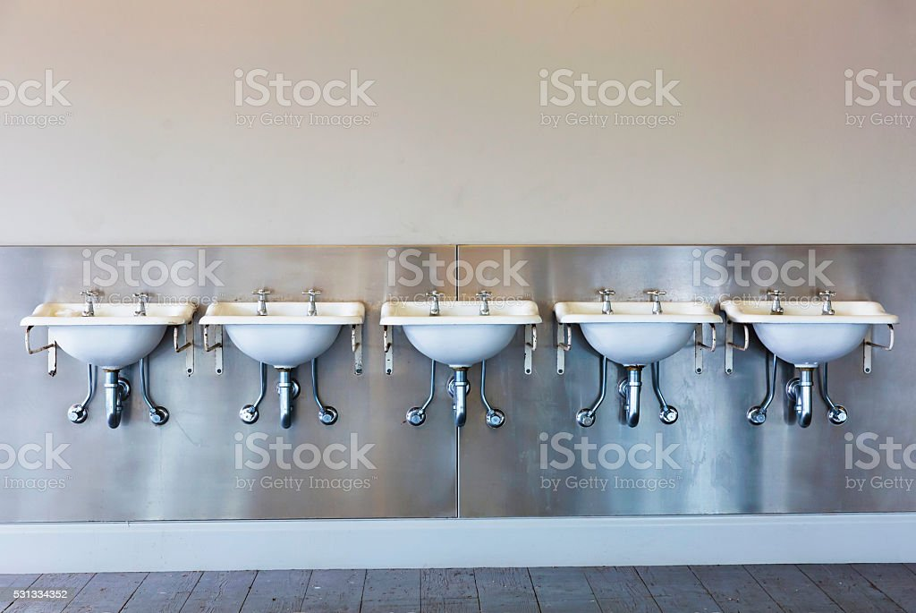 Row of old dirty sinks in publick restroom, copy space stock photo