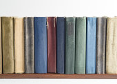 A row of old, faded, multicolored, yellowed books on a light background. Minimal style, copy space, side view
