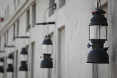 Glass and metal gas lanterns converted to electricity hanging on a wall in the United Arab Emirates