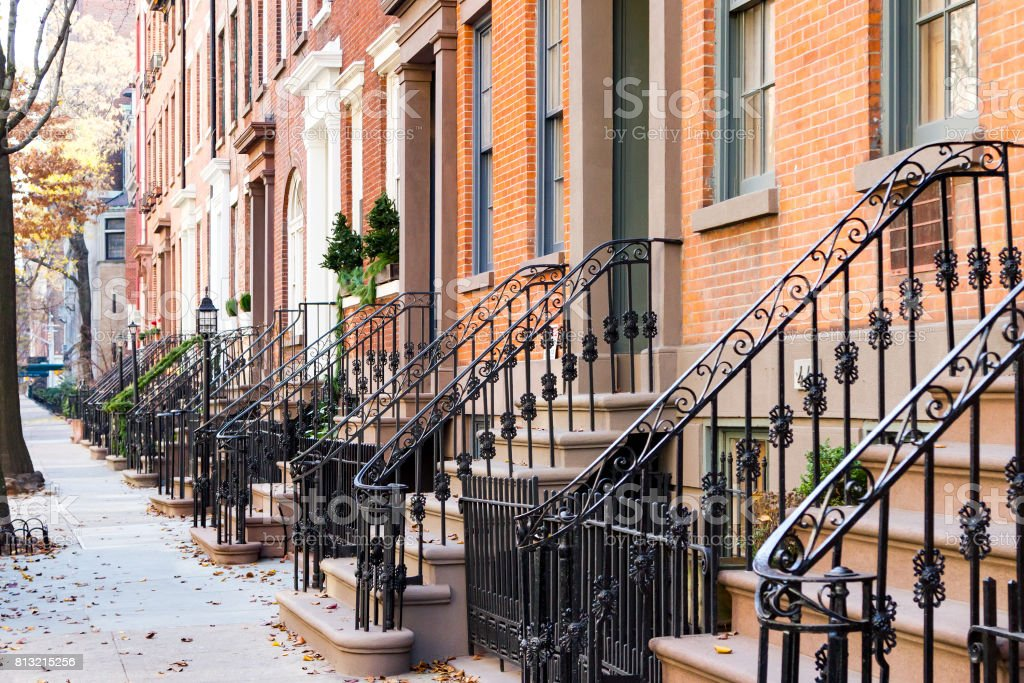 Row of old historic brownstone buildings along an empty sidewalk block in the Greenwich Village neighborhood of Manhattan, New York City NYC stock photo