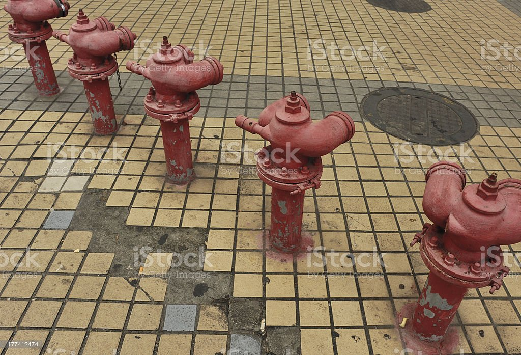 row of old red fire hydrant in street stock photo