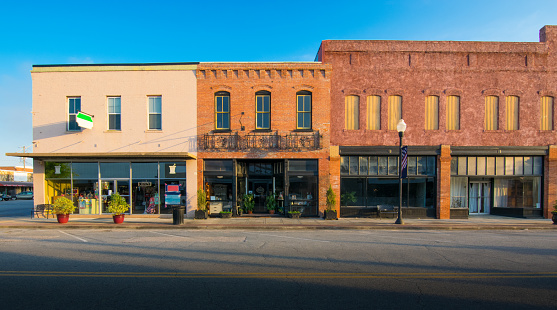 Storefront facades at dusk on a quiet street in a small Georgia town. The scene includes small retail shops in the evening light against a deep blue sky. The street and parking spaces are empty.