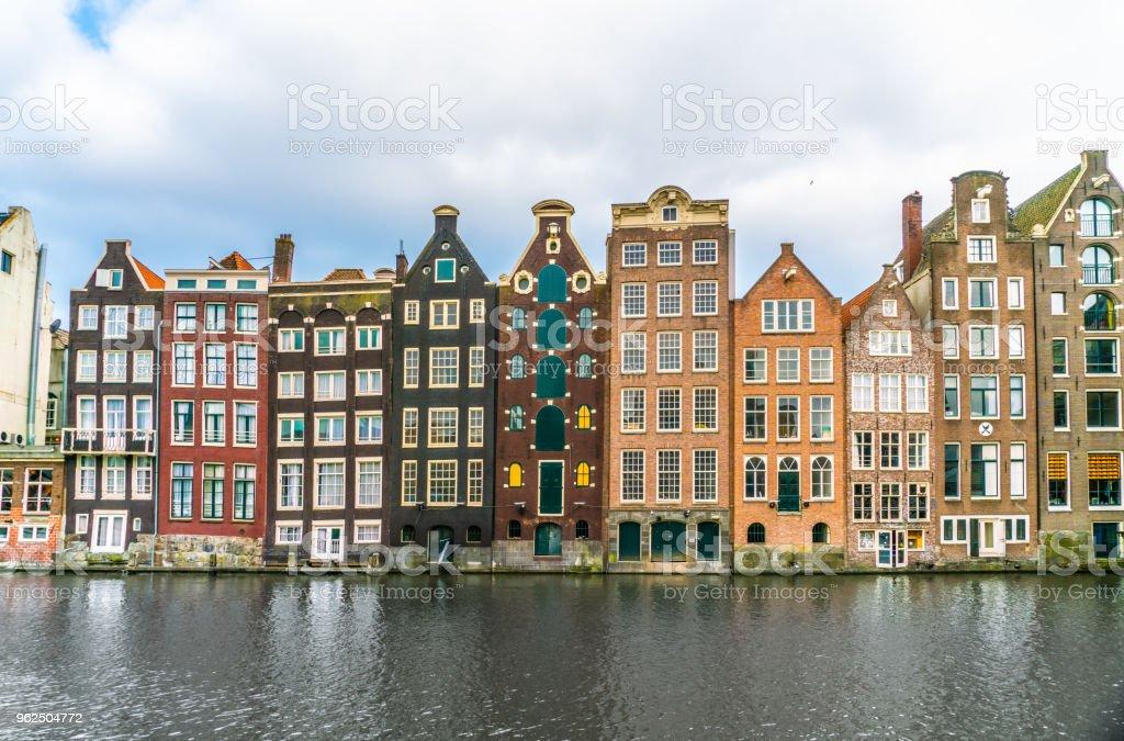 Uma fileira de casas tradicionais antigas na Damrak em Amesterdão - Foto de stock de Amsterdã royalty-free